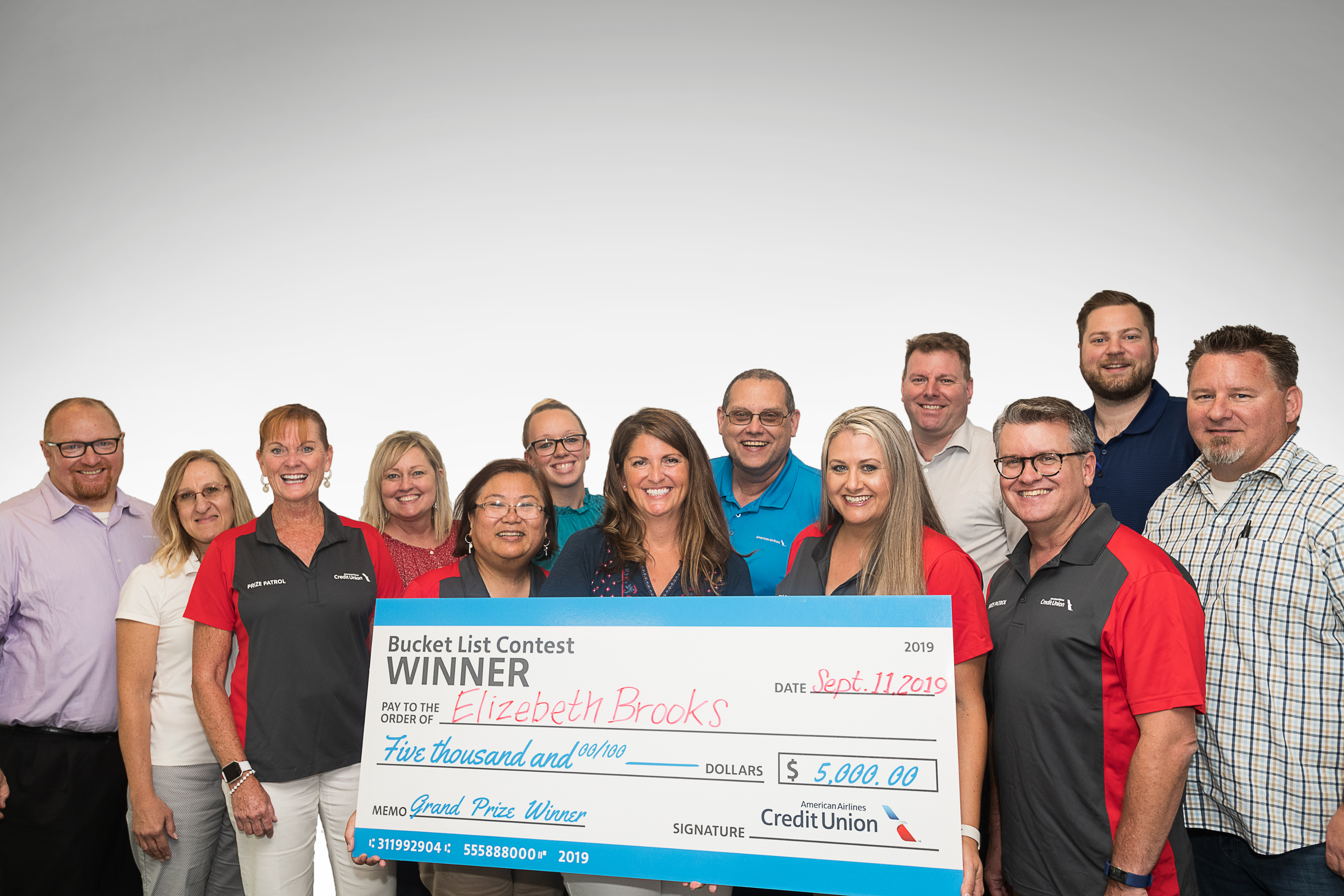 american airlines federal credit union employees holding big check with winner